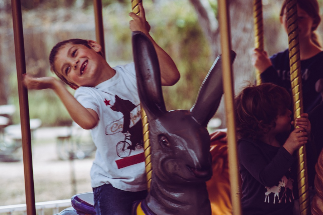 Boy in White T-shirt Riding Carousel