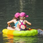 Canva - Two Girls in Floating and Paddling Using Badminton Rackets